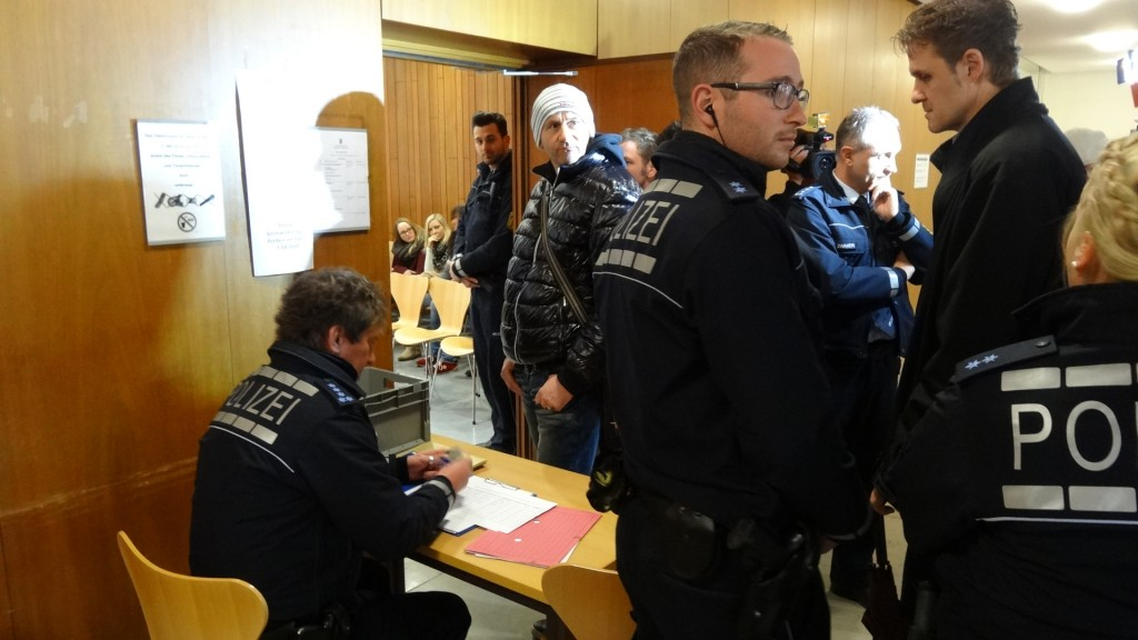 """Der 5 Sterne Polizist Müller, (angeleuchtet in der Mitte) versucht ständig, die TV-Teams zu reglementieren. Ein Journalist wird über die Anstandslinie von Polizist Müller bedrängt, mit den Worten – """"Wenn sie mir zu nahe kommen - werde ich sie aus dem Gericht entfernen lassen"""". Solche Provokationstricks sind bekannt - wird vom Journalisten erwidert."""