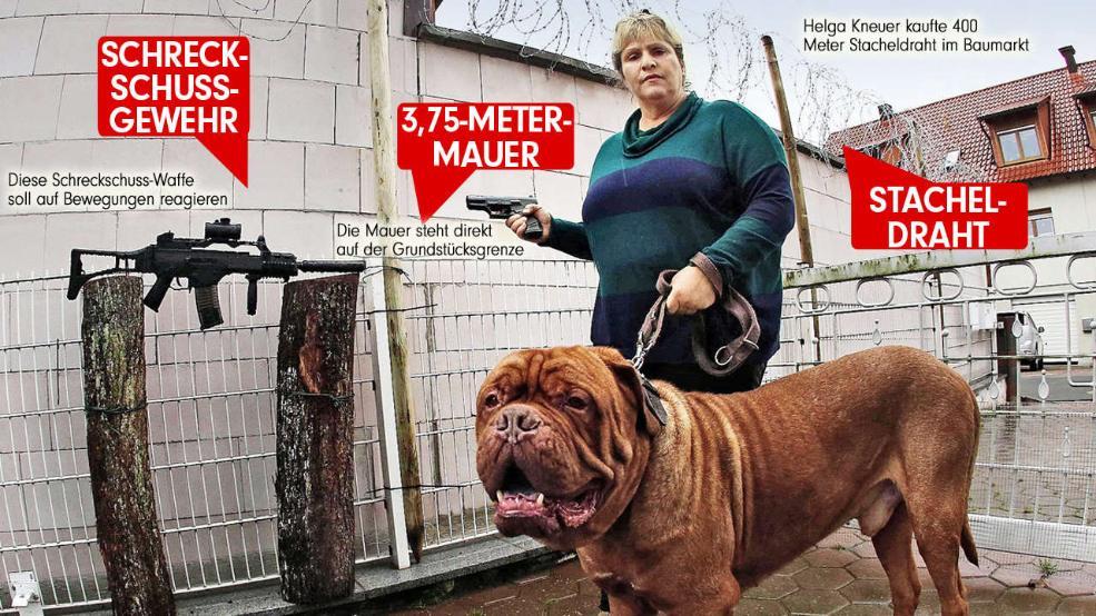 Helga Kneuer (45) steht mit ihrer Bordeaux-Dogge Brix und einer Schreckschusspistole an der ihr verhassten Mauer Foto: Daniel Löb
